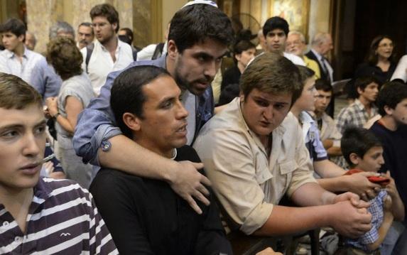 Un joven trata de frenar la actitud de un grupo de católicos que irrumpieron durante la ceremonia. Foto: DyN